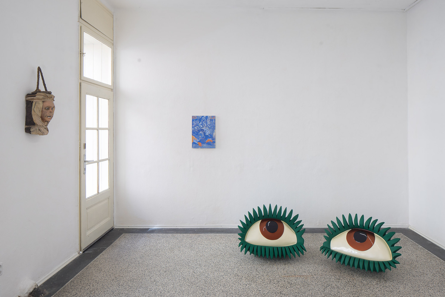 head sculpture, eyes sculpture and painting in a room